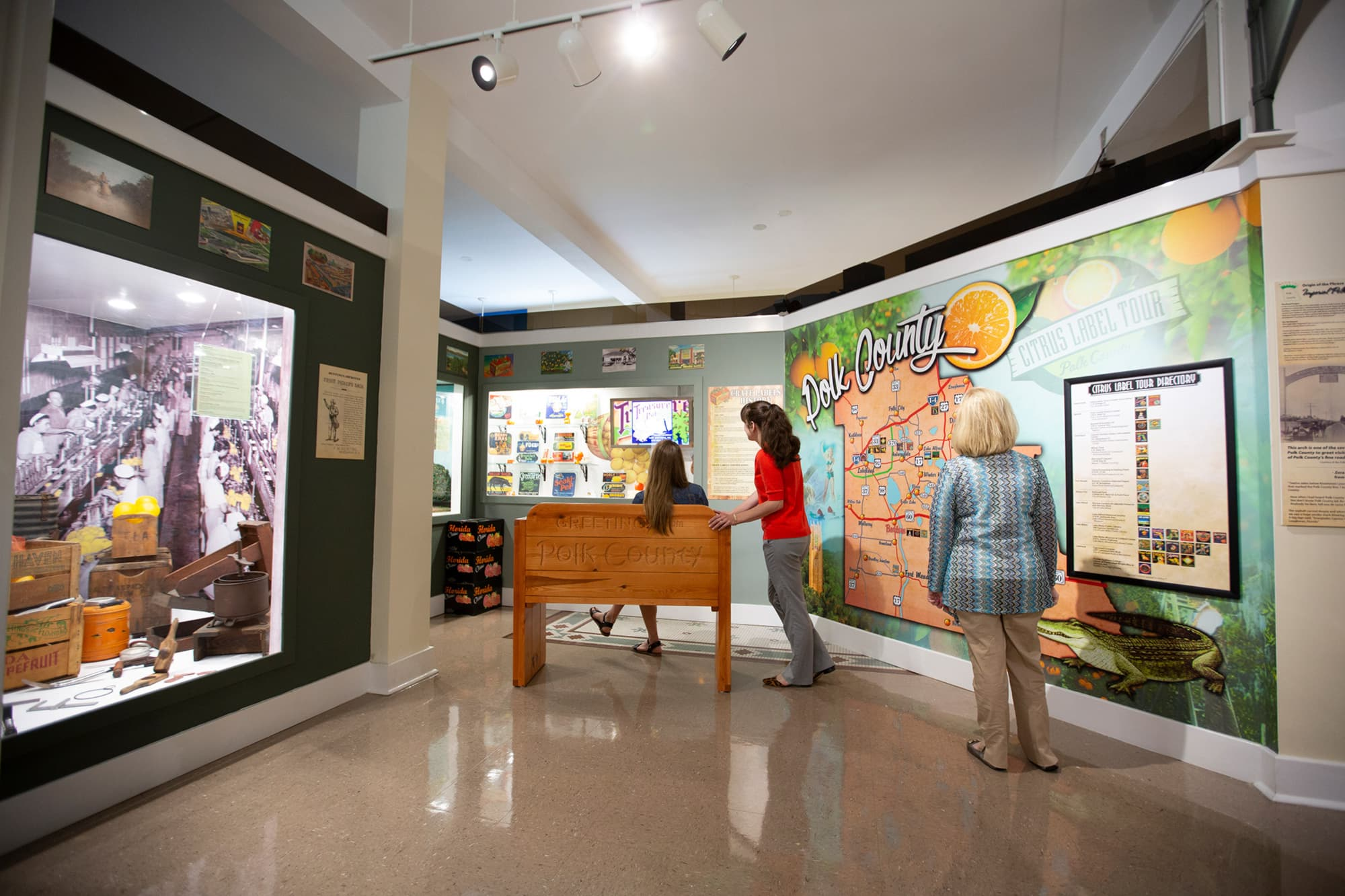 3 women looking at citrus themed Polk County exhibits inside Polk County History Center in Bartow, FL