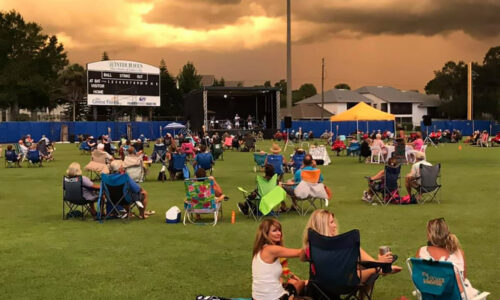 groups of people sitting outside at sunset during a concert at Chain O Lakes stadium