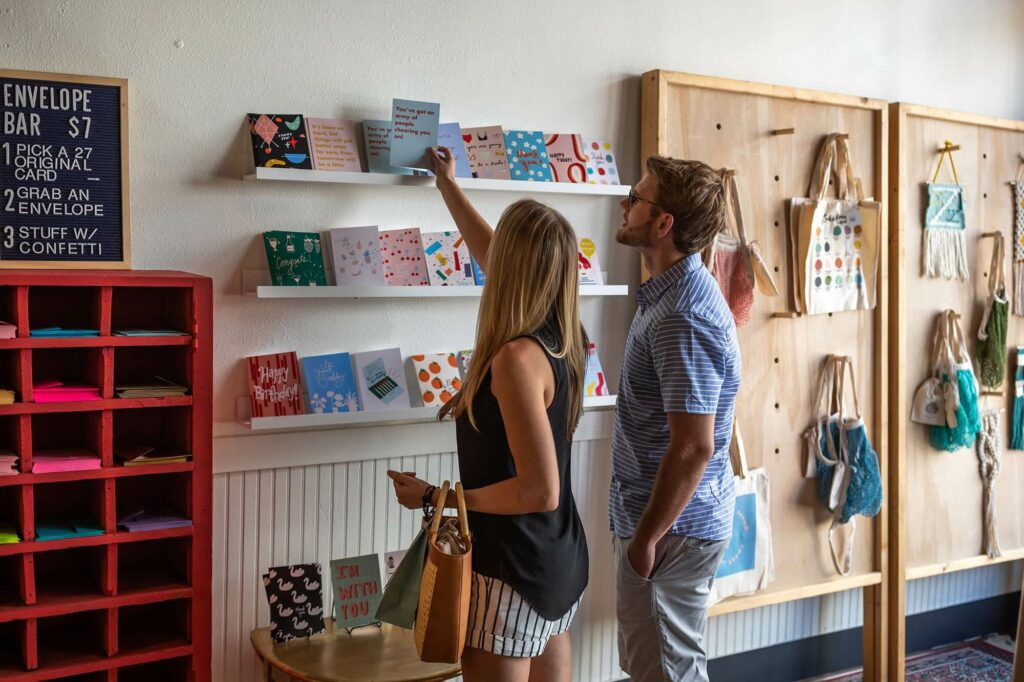 two adults looking at greeting cards on wall display at Twenty Seven in Lakeland, FL