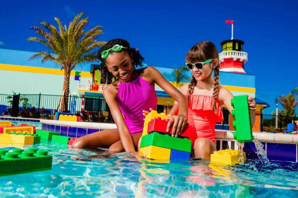 2 young girls playing with LEGO bricks in LEGOLAND Beach Retreat pool