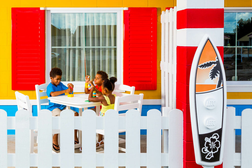3 kids sitting at front porch table outside LEGOLAND Beach Retreat bungalow