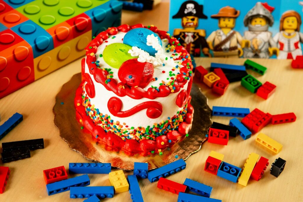 birthday cake with legos and lego pirates in background