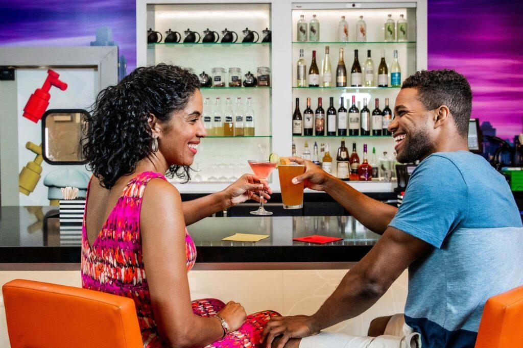 2 adults enjoying cocktails at Skyline Lounge inside onsite hotel at LEGOLAND