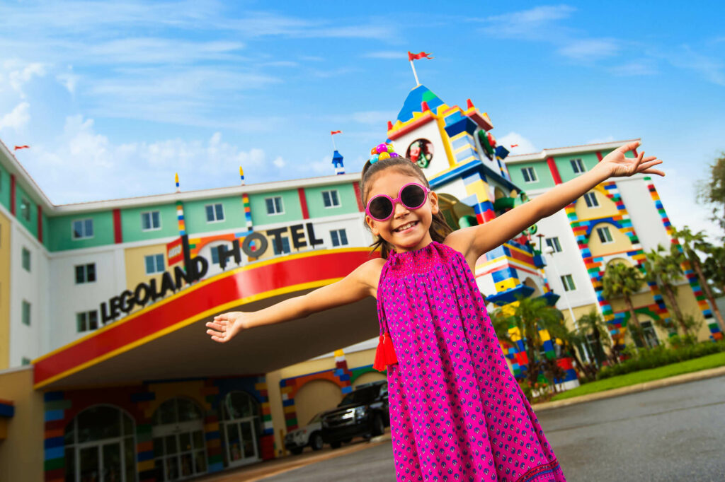young girl in pink dress and pink sunglasses outside LEGOLAND Hotel in Winter Haven, FL