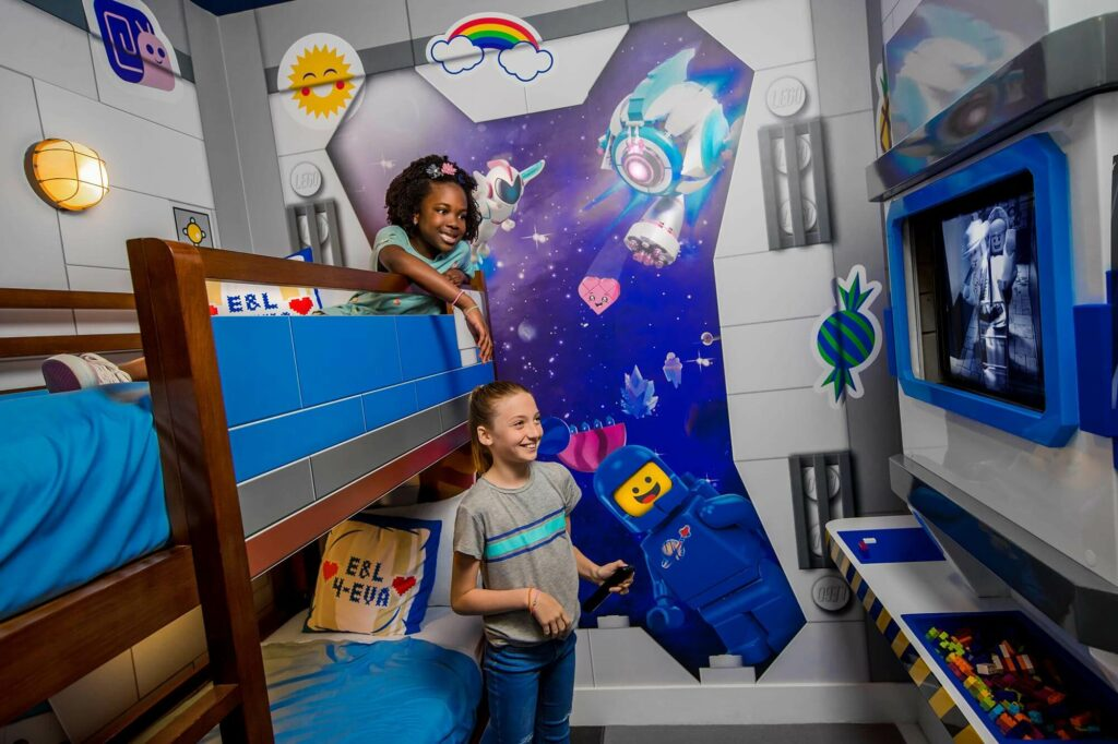 2 girls kids room with bunk beds and TV in LEGO Movie World themed room at LEGOLAND Hotel in Florida.