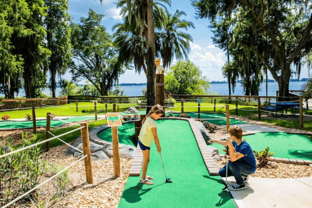 2 kids playing mini golf near a lake at Hotel