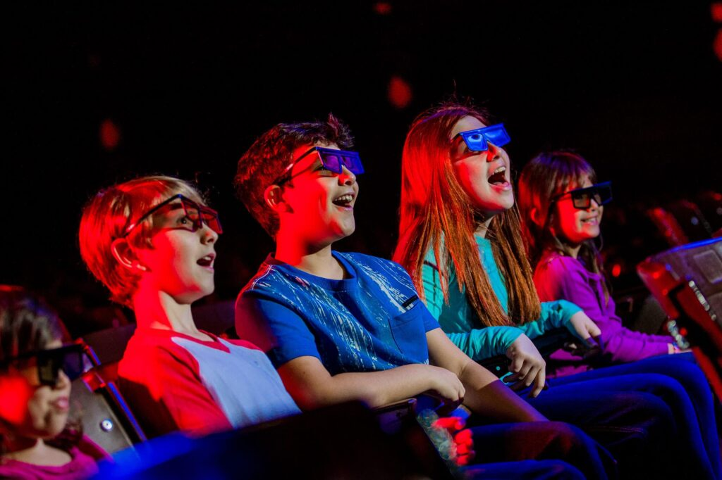 5 kids wearing 3D glasses inside LEGOLAND Fun Town Theater in Florida