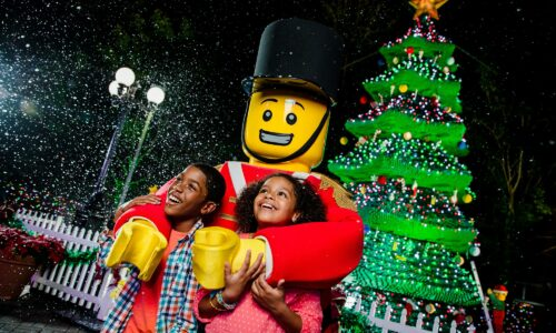 Santa and 2 kids with Christmas tree in background during Holidays at LEGOLAND