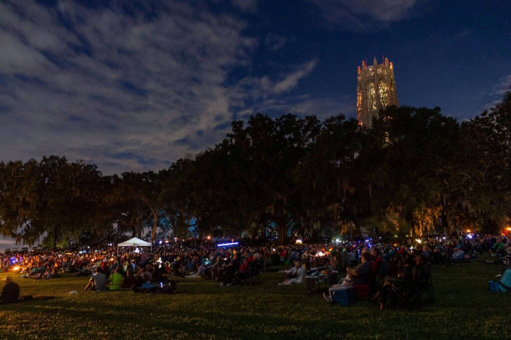 crowd gathered for moonlight concert at Bok Tower Gardens. Carillon tower in background.