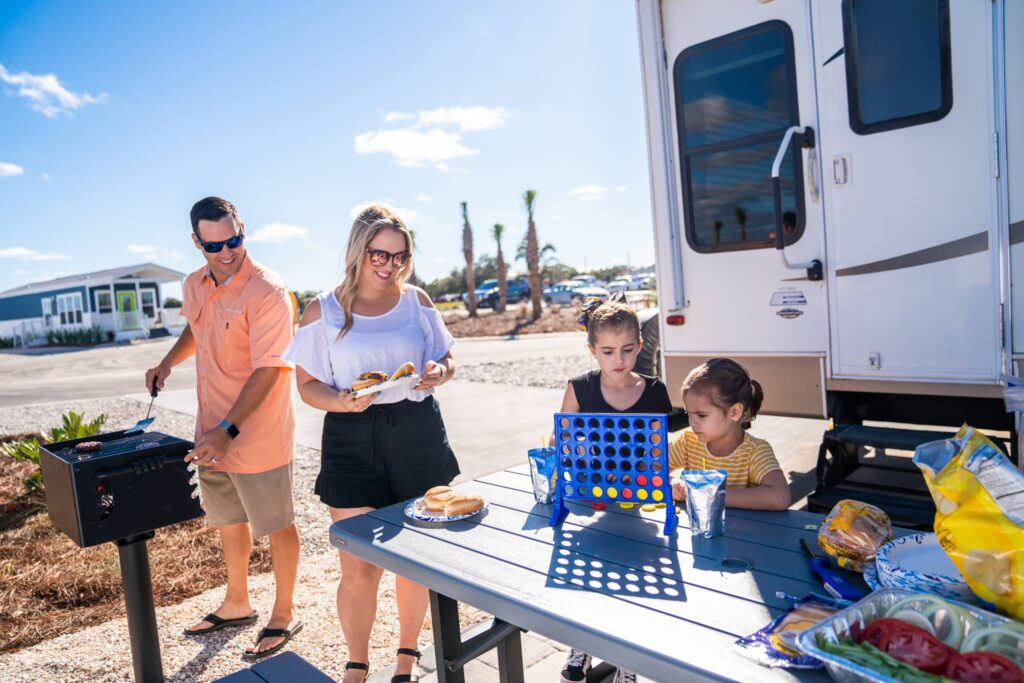 family of 4, grilling and playing games on picnic table next to motorhome at Cabana Club RV Resort in Auburndale FL