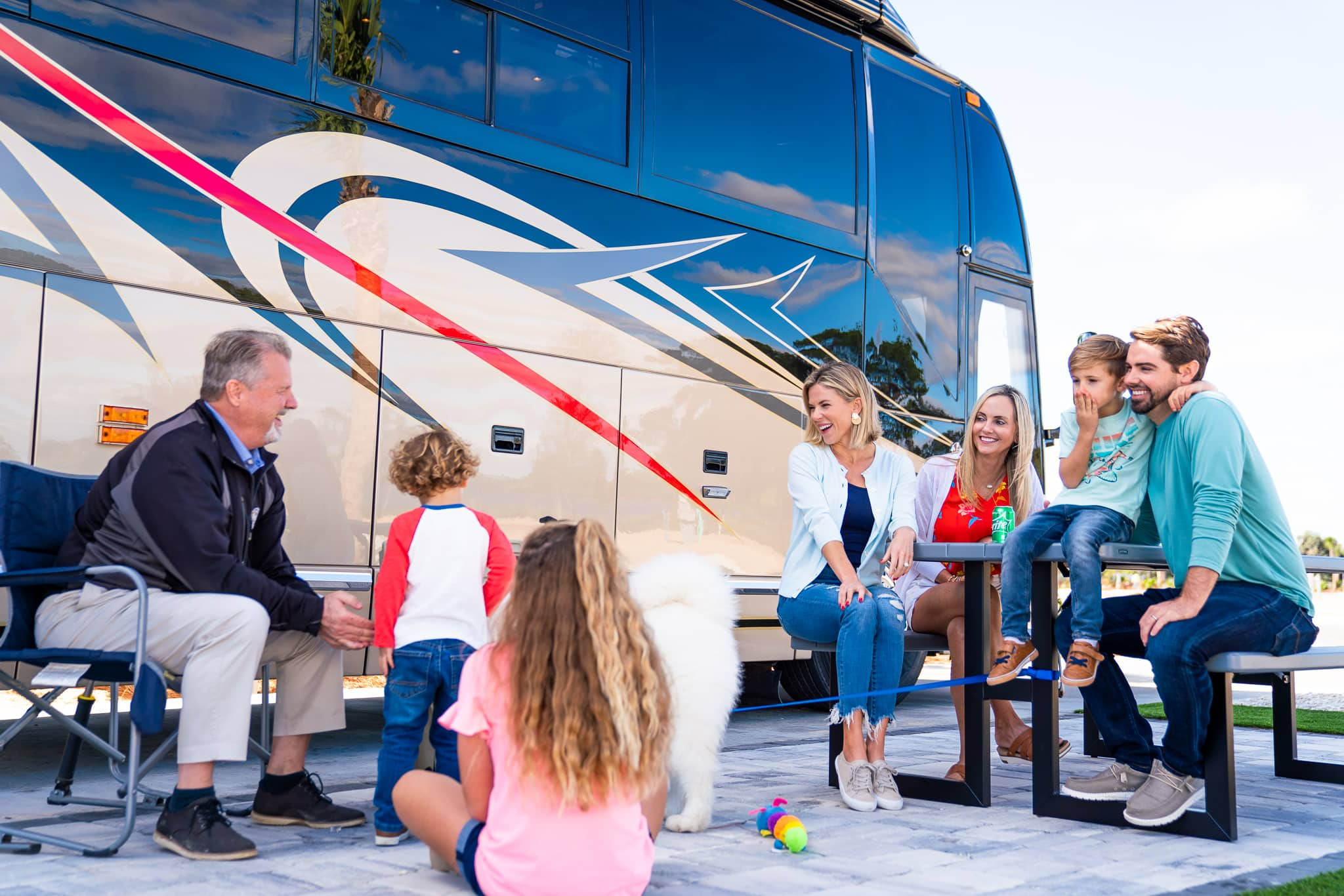 multi-generation family and dog sitting outside motorhome at Cabana Club RV Resort in Auburndale FL