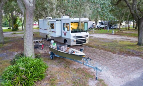 Motorhome and boat under an oak tree at Camp Mack, a Guy Harvey Resort, RV campsite near Lake Wales, FL