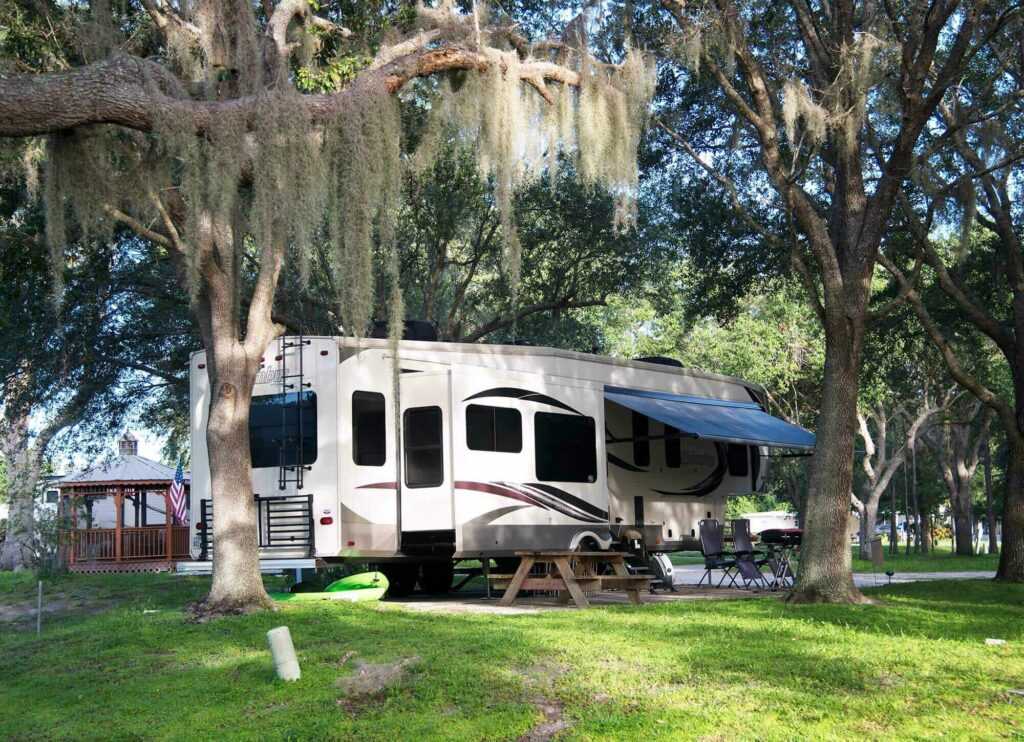 RV Motorhome on shaded campsite at Camp Mack, a Guy Harvey Resort in Lake Wales, FL