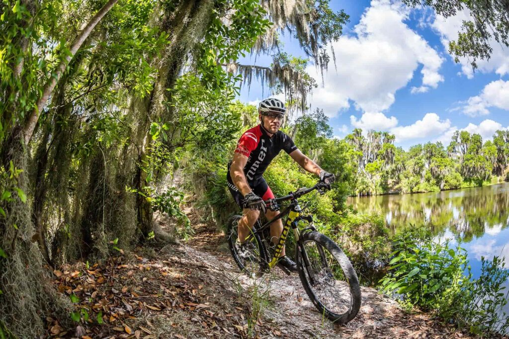 cyclist riding Niner bike at Loyce Harpe Park mountain bike trail system in Mulberry, FL