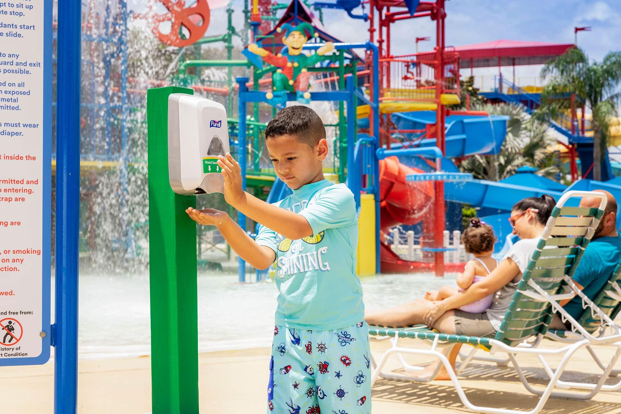 Child using hand Sanitizer station at LEGOLAND Water Park in Winter Haven, FL