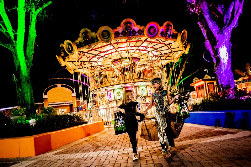 Two kids in costume at the carousel